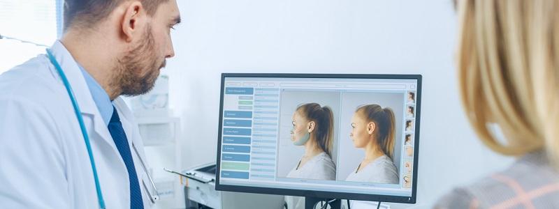 Médico demonstrando em um computador o antes e depois da cirurgia plástica para a sua paciente.