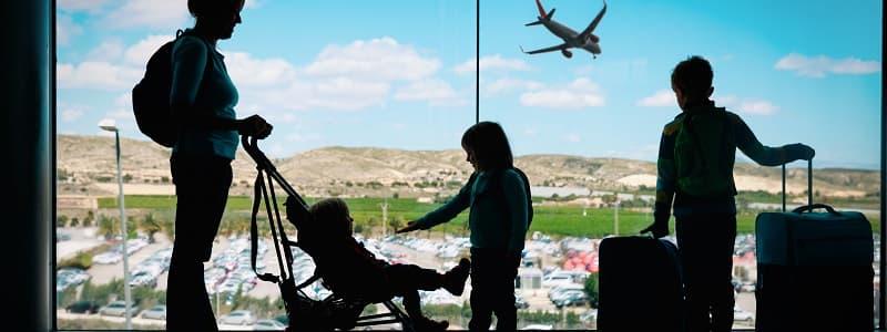 Mãe com três filhos no aeroporto observando um avião