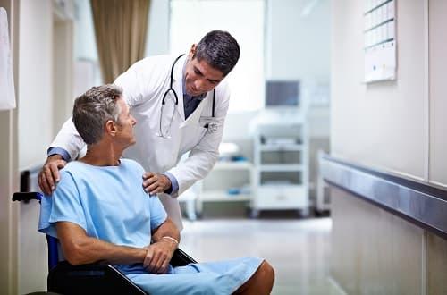 Médico conversando com paciente sentado em cadeira de rodas
